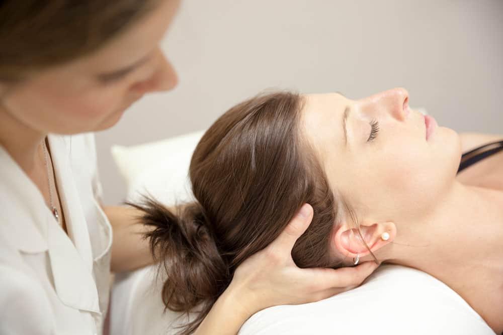 Osteopathin massiert Kopf einer Patientin