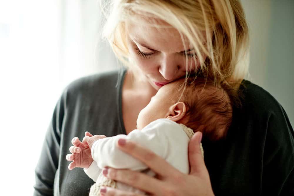 Mama hält Baby im Arm und küsst es auf die Stirn