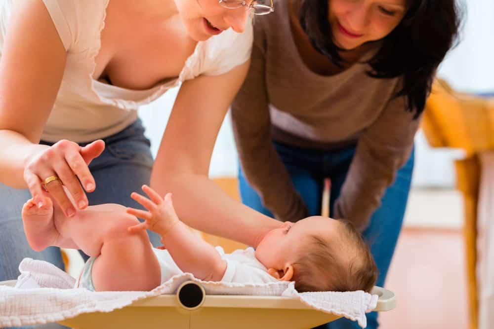Hebamme und Mutter wiegen ein Baby