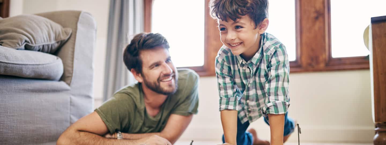 Vater und Kind spielen auf dem Teppich