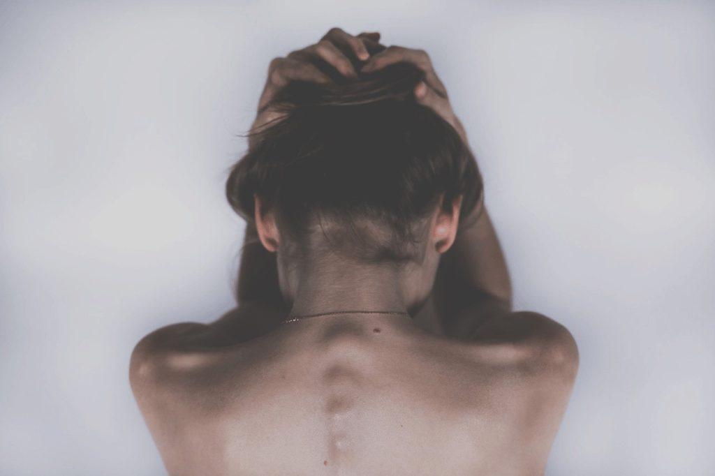 Eine Frau von hinten, die Ihre Hände über dem Kopf zusammenschlägt