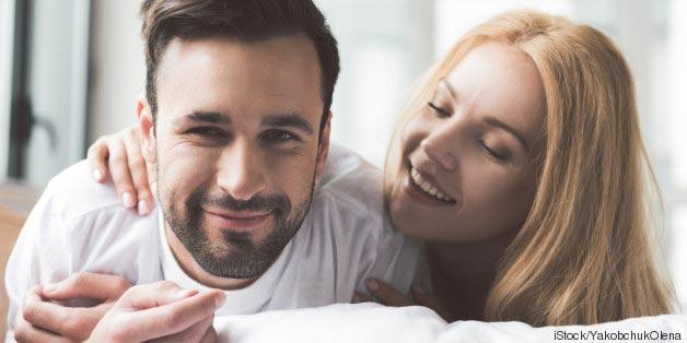 Ein Mann und eine Frau liegen glücklich zusammen im Bett