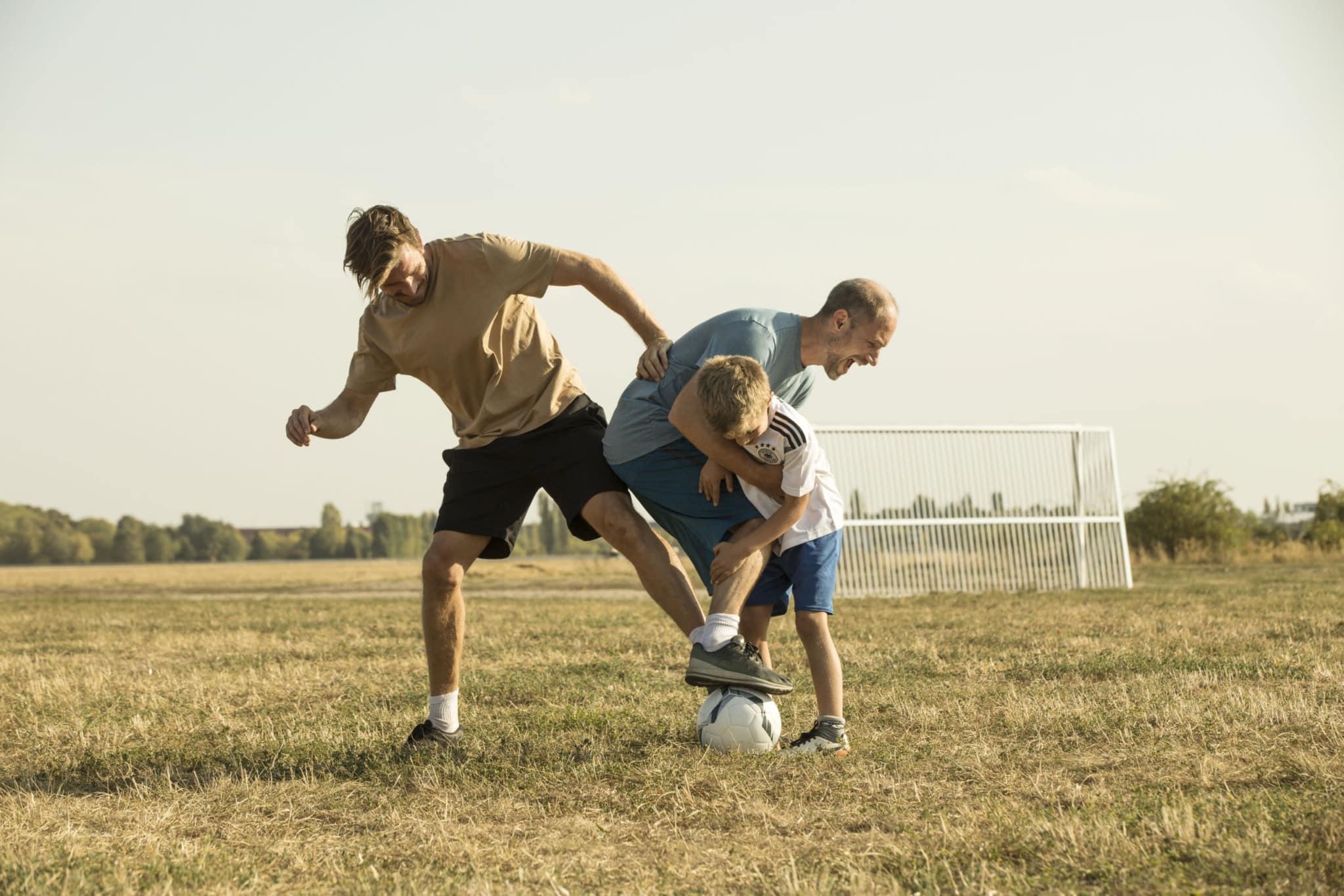 Zwei junge Männer und ein Junge spielen draußen Fußball.