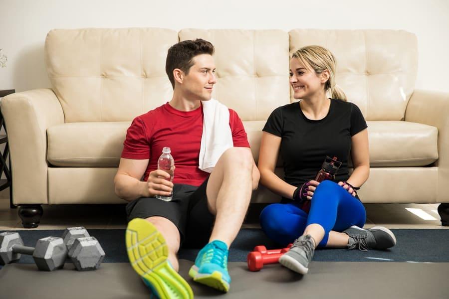 Mann und Frau sitzen nach dem Sport vor einem Sofa