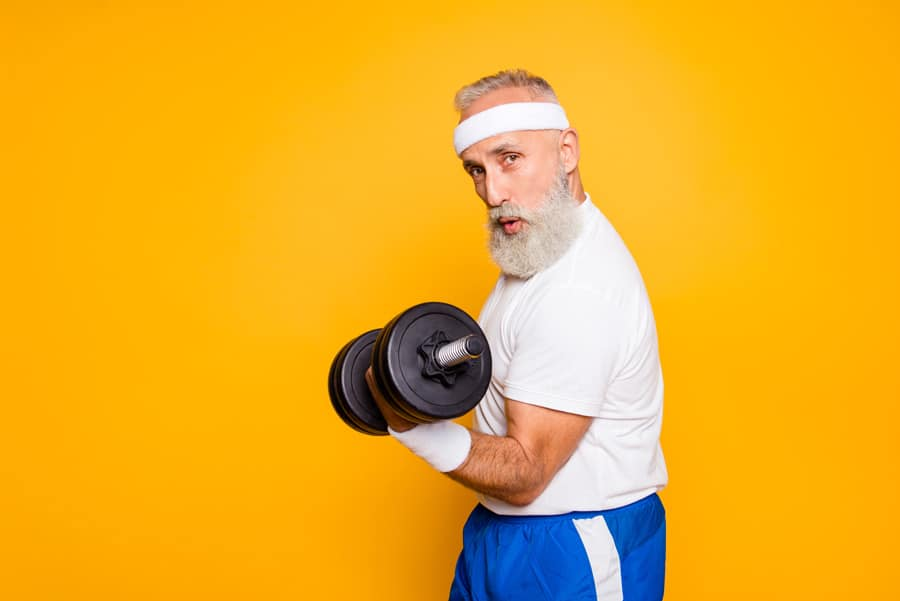 Älterer Mann posiert mit Hantel