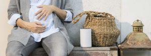 Schwangere sitzt neben einem Alexa Bluetooth-Lautsprecher