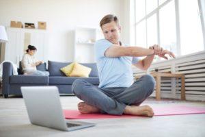 Mann dehnt sich sitzend vor einem Laptop