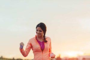Eine Frau in Sportkleidung ballt erfreut die Faust