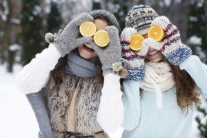 Zwei Frauen stehen lachend in einer Winterlandschaft und halten sich Zitronen vor die Augen.