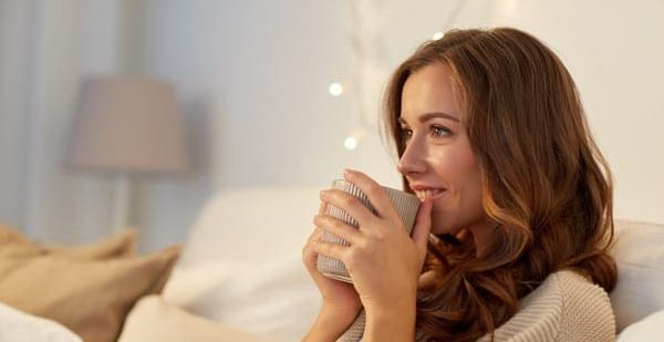Glückliche Frau sitzt gemütlich mit einer Tasse auf dem Sofa