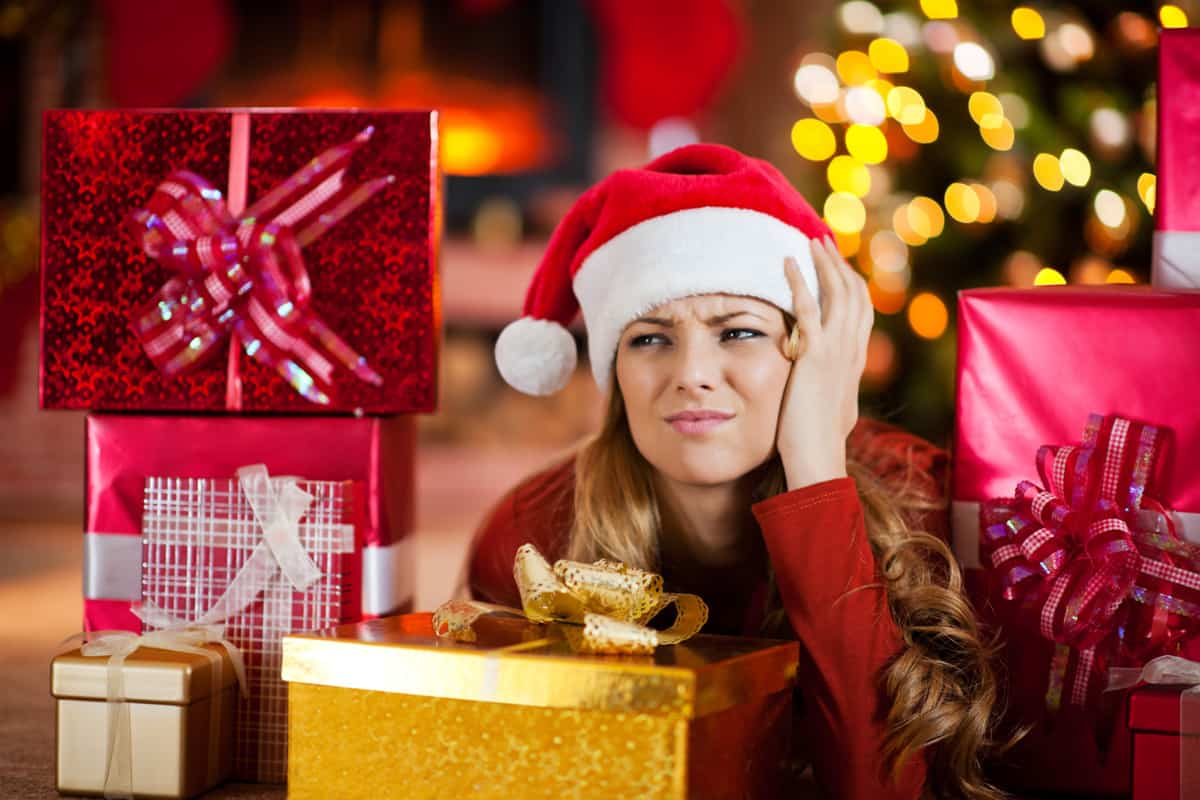 Eine Frau sitzt mit genervtem Gesichtsausdruck zwischen mehreren, verpackten Geschenken.