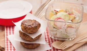 Drei gestapelte Frikadellenn stehen neben einer Schale Kartoffel-Radieschen-Salat