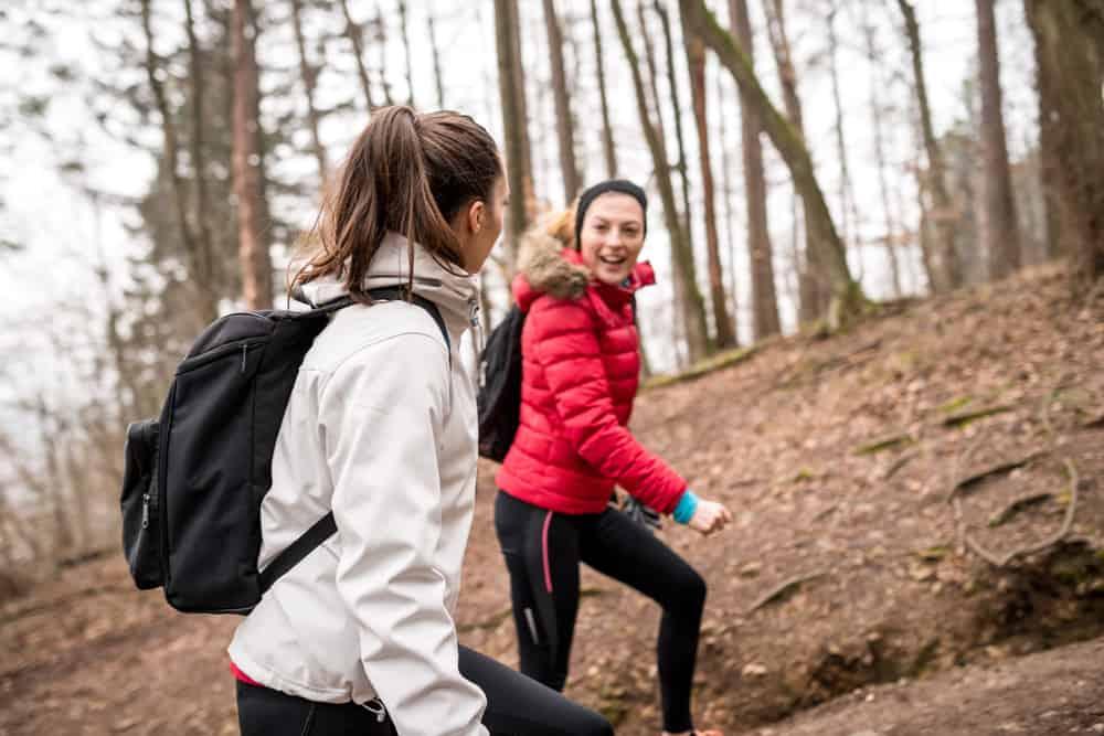 zwei Frauen wandern bei kaltem Wetter durch den Wald