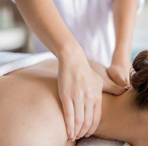 Die Hände einer Masseurin im Nacken einer Patientin