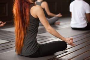 Junge Frau mit langen roten Haaren sitzt im Schneidersitz beim Yoga