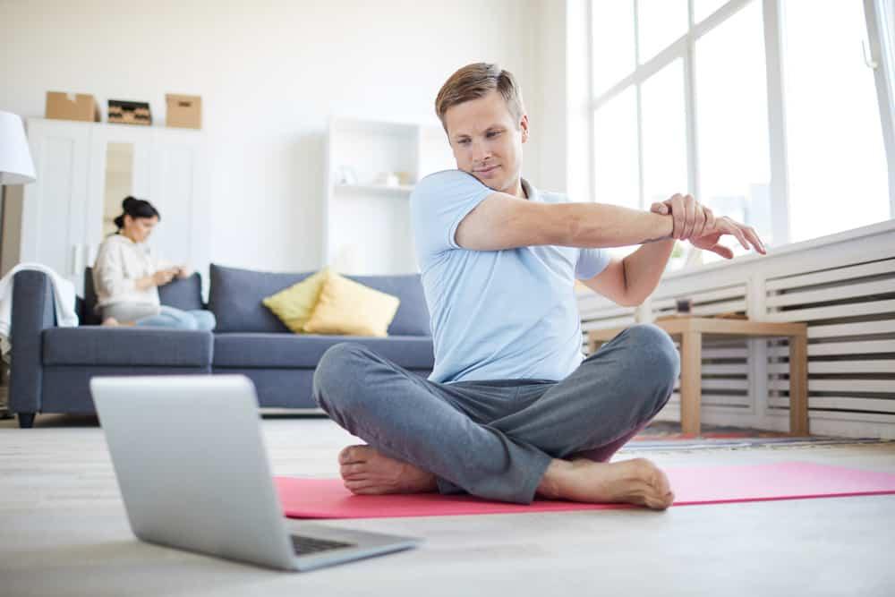 Mann im Wohnzimmer macht yoga vor dem Laptop