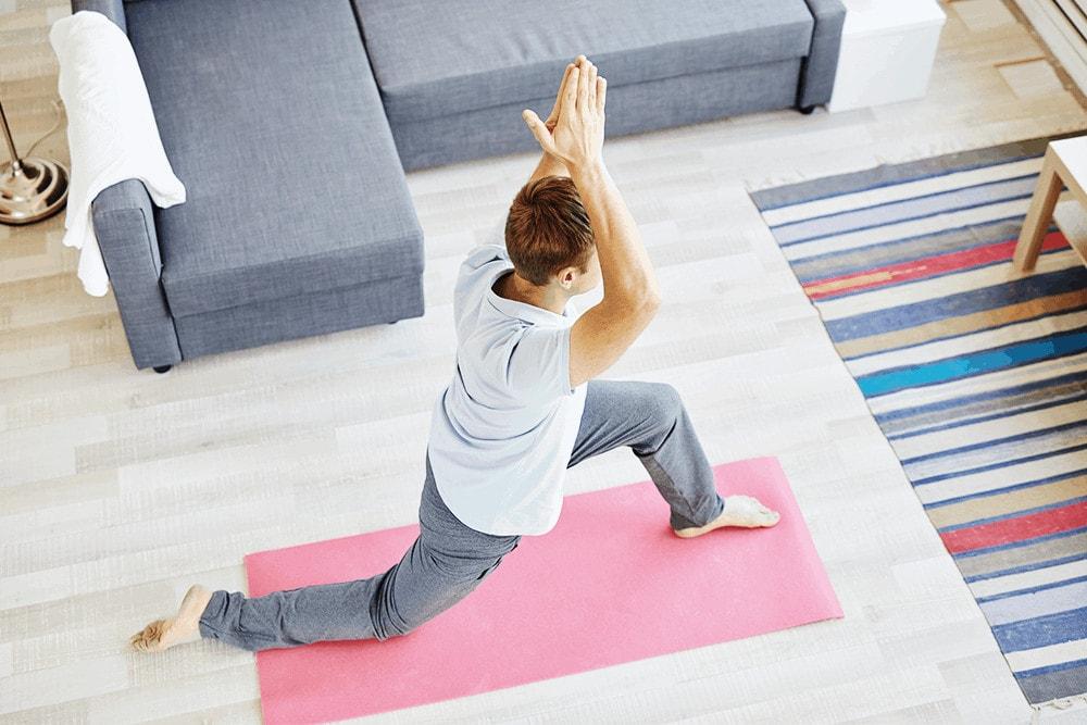 Ein Mann macht eine Yoga-Übung bei sich zu Hause
