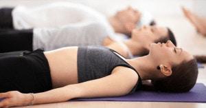 Drei Personen liegen entspannt auf Yogamatten