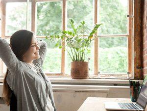 Ein Frau lehnt sich an ihrem Schreibtisch zurück. Sie fühlt sich offensichtlich wohl