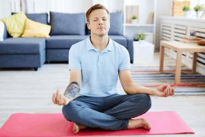 Ein Mann sitzt in Meditationshaltung auf einer Yogamatte