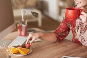 Eine Frau nimmt eine Erdbeere von einem Teller mit Obst