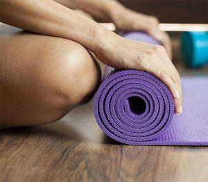 Nahaufnahme wie jemand eine Yoga-Matte einrollt