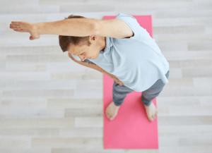 Ein Mann macht eine Yoga-Übung auf einer Matte