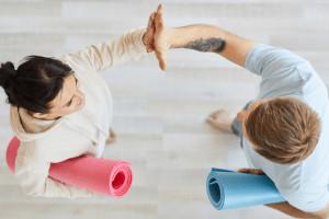 Ein Mann und eine Frau klatschen sich ab. Sie haben Yoga-Matten unter den Armen