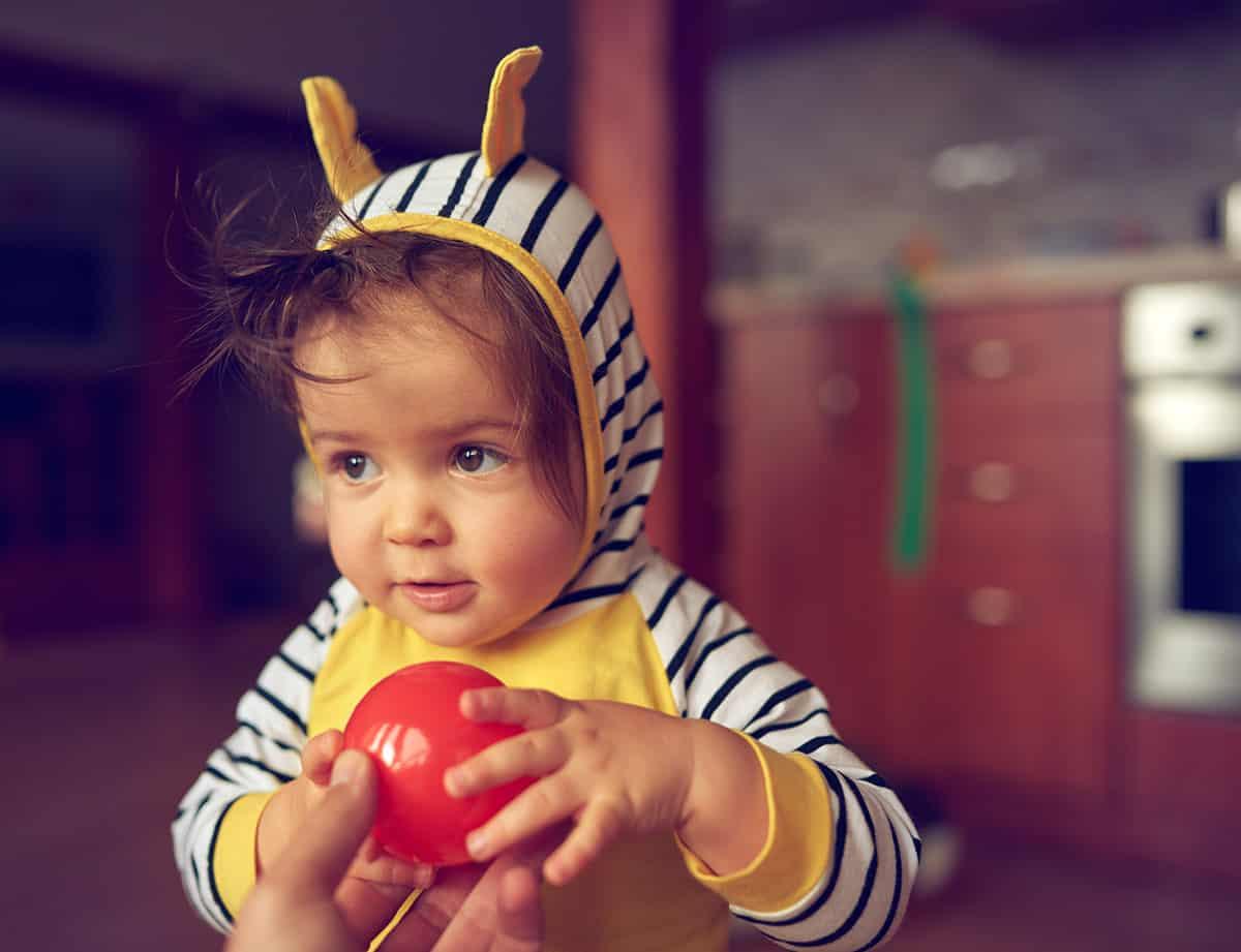 Ein Kleinkind bekommt einen roten Ball von einem Erwachsenen gereicht