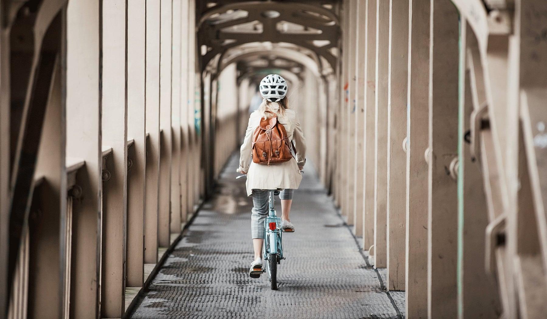 Eine Frau mit Helm auf einem Fahrrad