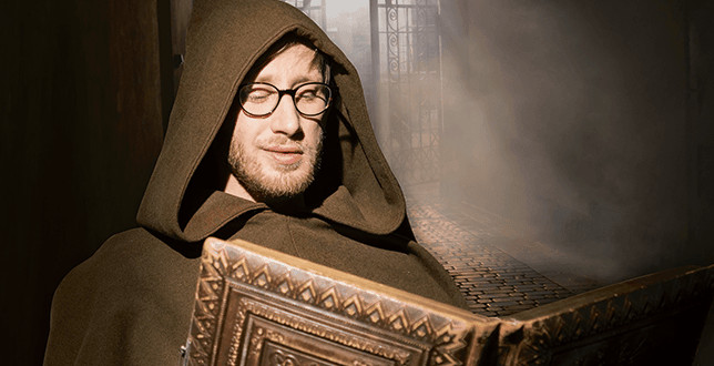 """Der Hauptdarsteller des Kinospots """"KNAPP was?"""" der Knappschaft, in einer braunen Robe mit einem alten Buch"""