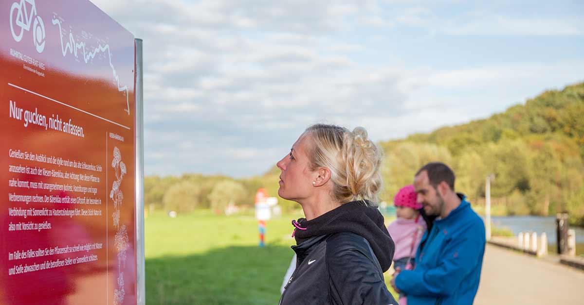 Eine Frau schaut auf dem Ruhrtal-Radweg auf eine Info-Tafel der Knappschaft