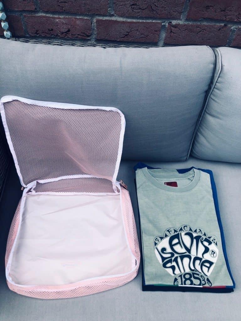 Bisher nicht gerollte T-Shirts neben einer Tasche