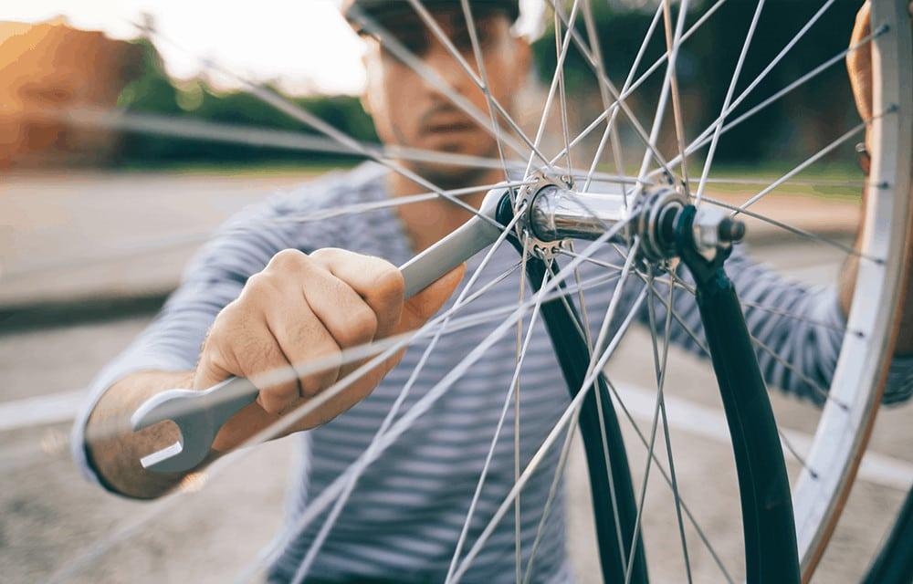 Nahaufnahme eines Mannes, der einen Fahrradreifen anbringt.