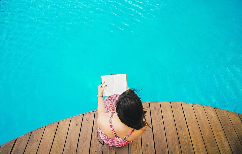 Eine Frau an einem Pool liest in einem Buch etwas über Hitze