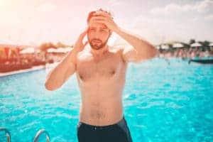Ein Mann kommt aus dem Pool und hält sich den schmwerzenden Kopf