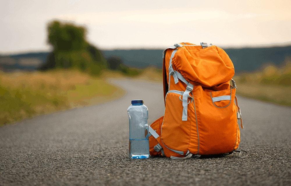 Ein Rucksack und eine Trinkflasche allein auf einer Straße