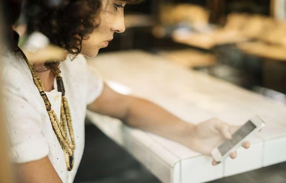 Eine Frau wählt auf ihrem Smartphone den Auslandsnotruf der Knappschaft