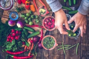 Jemand legt verschiedene Gemüsesorten in Salzlake ein