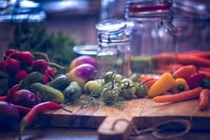 Verschiedene Gemüsesorten und Einmachgläser auf einem Tisch
