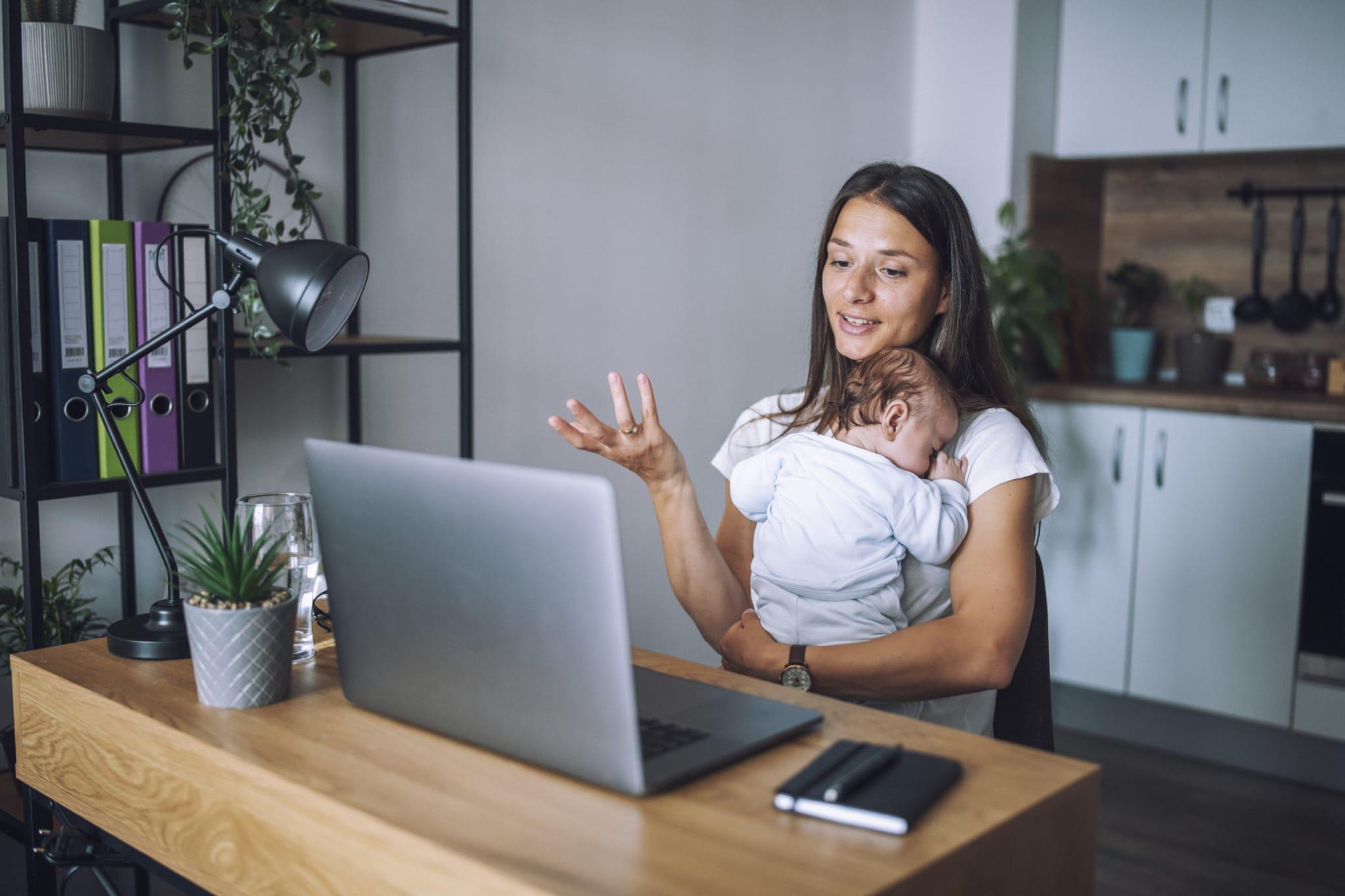 Junge Mutter mit Baby auf dem Arm nutzt den Ärzte-Videochat