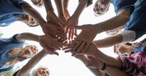 Eine Gruppe Menschen hält die Hände übereinander um Zusammenhalt zu demonstrieren.