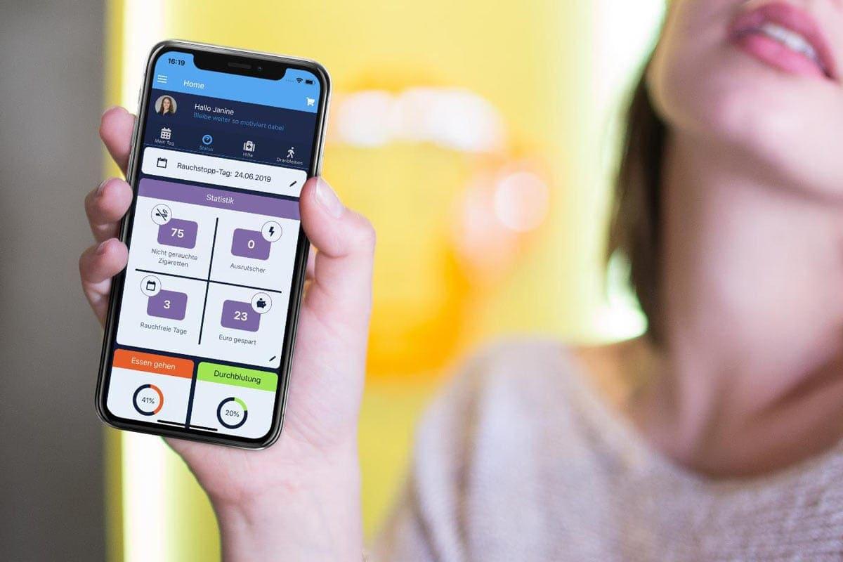 Eine Junge Frau hält ihr Smartphone in die Kamera, auf dem die Nichtraucherhelden App zu sehen ist.