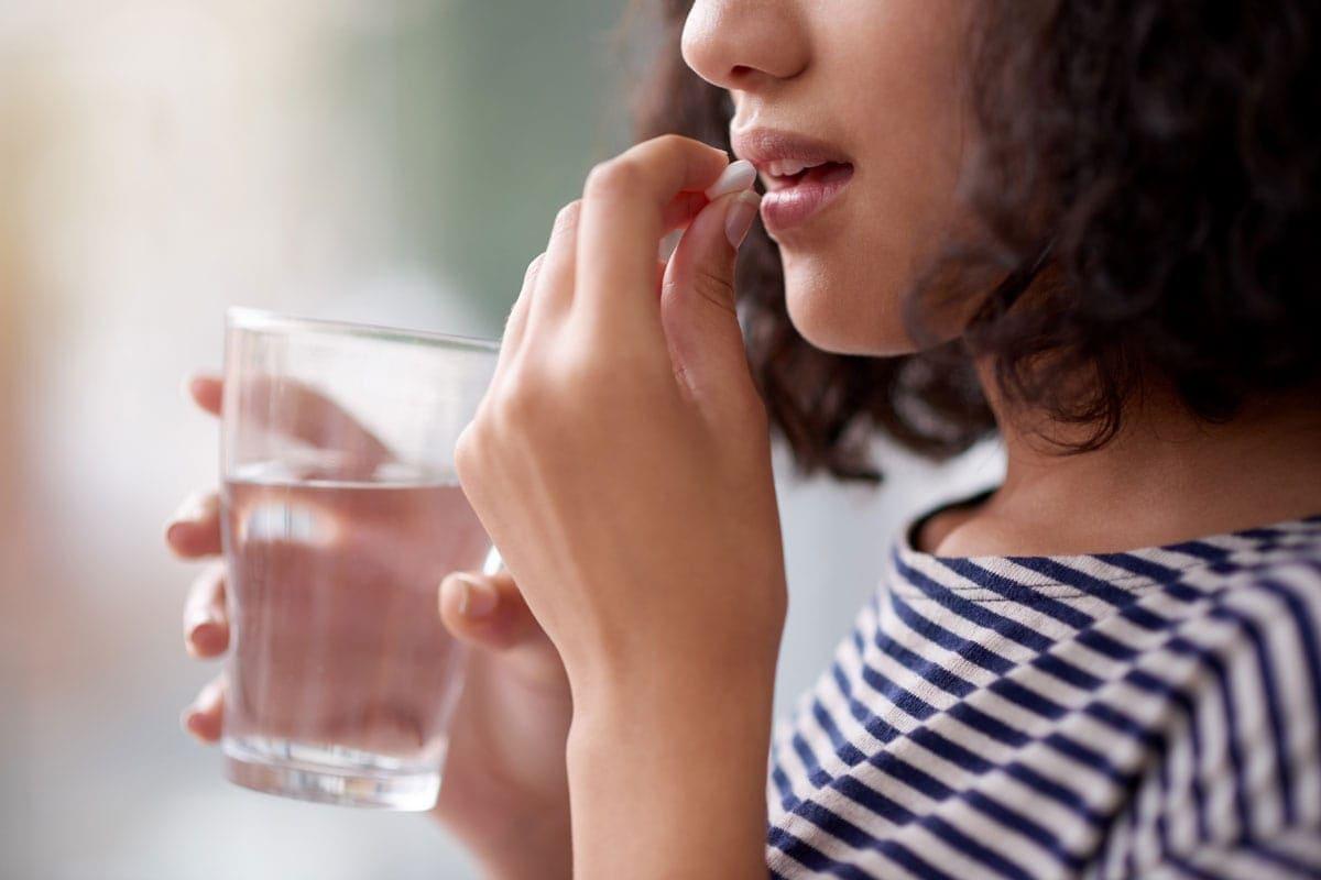 Eine junge Frau nimmt Antibiotika.