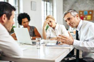 Vier Kollegen im Büro in einem anscheinend psychisch belastenden Gespräch