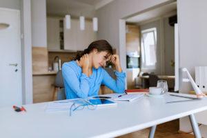 Eine junge Frau im Homeoffice wirkt gestresst
