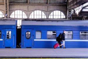 Ein junger Mann vor einem Zug am Bahnsteig