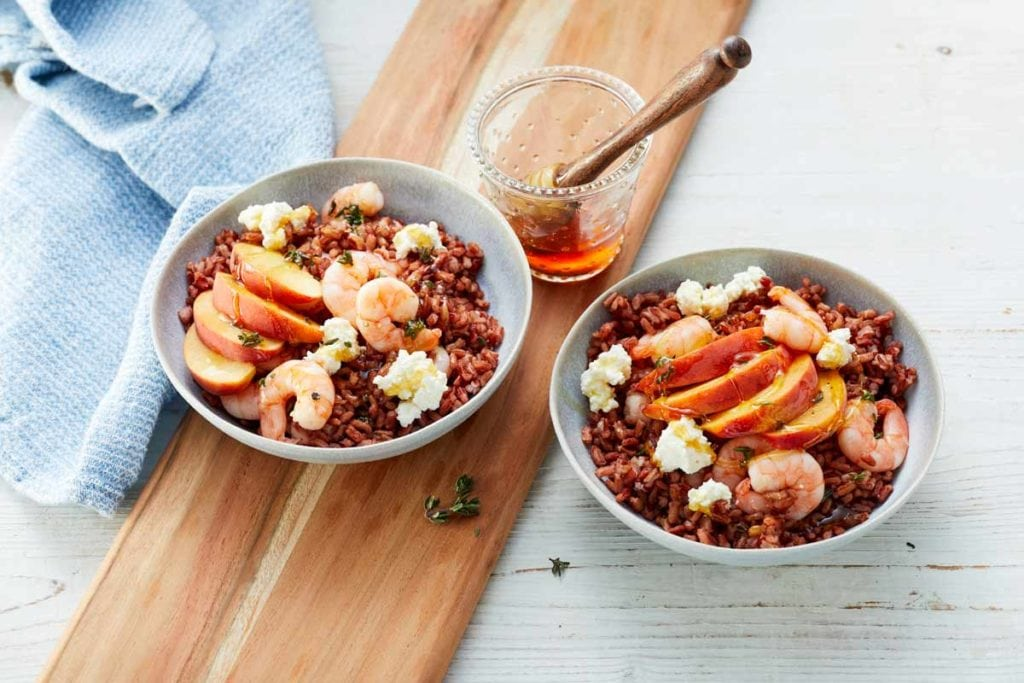 Zwei Schalen mit dem fertigen roten Reissalat mit Pfirsich