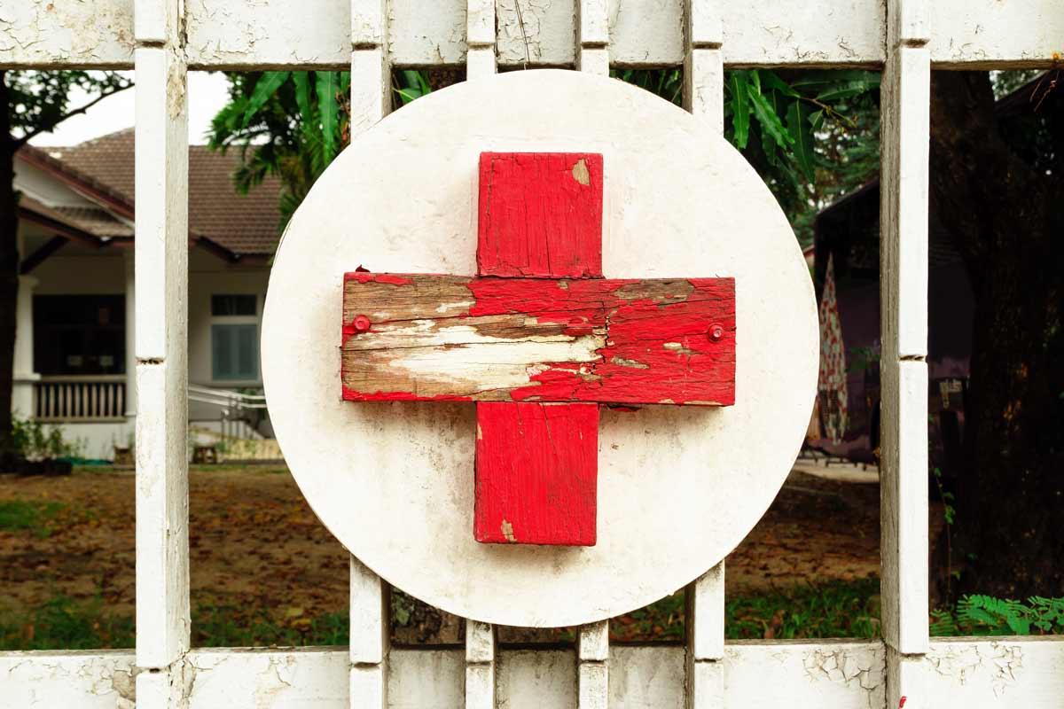 Nahaufnahme eines roten Kruezes auf einem Tor einer Klinik im Ausland