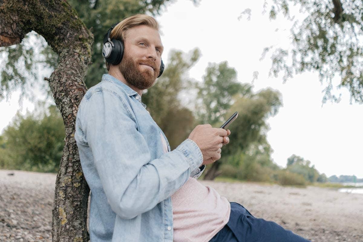 Ein Mann sitzt an einem Baum und genießt die Natur